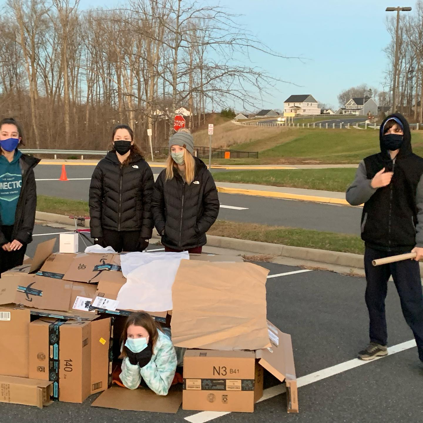 students outside with cardboard box houses