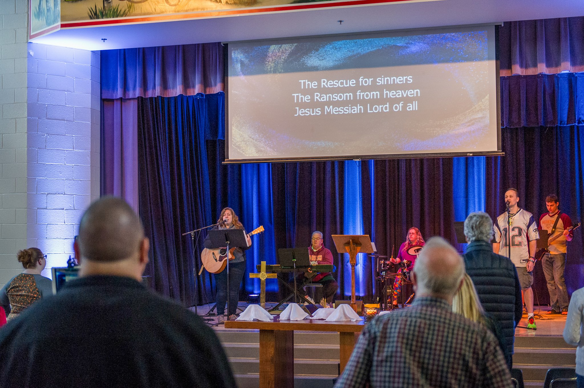view of worship from behind a row of people, band on the stage