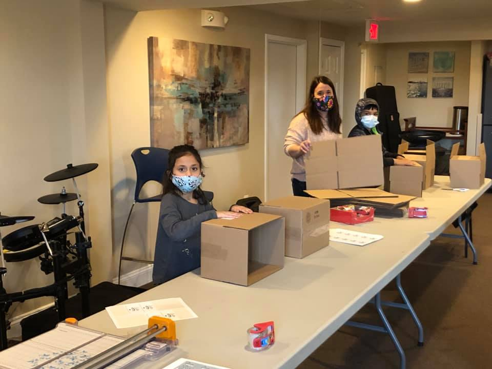 a family packing boxes for a service project while wearing masks